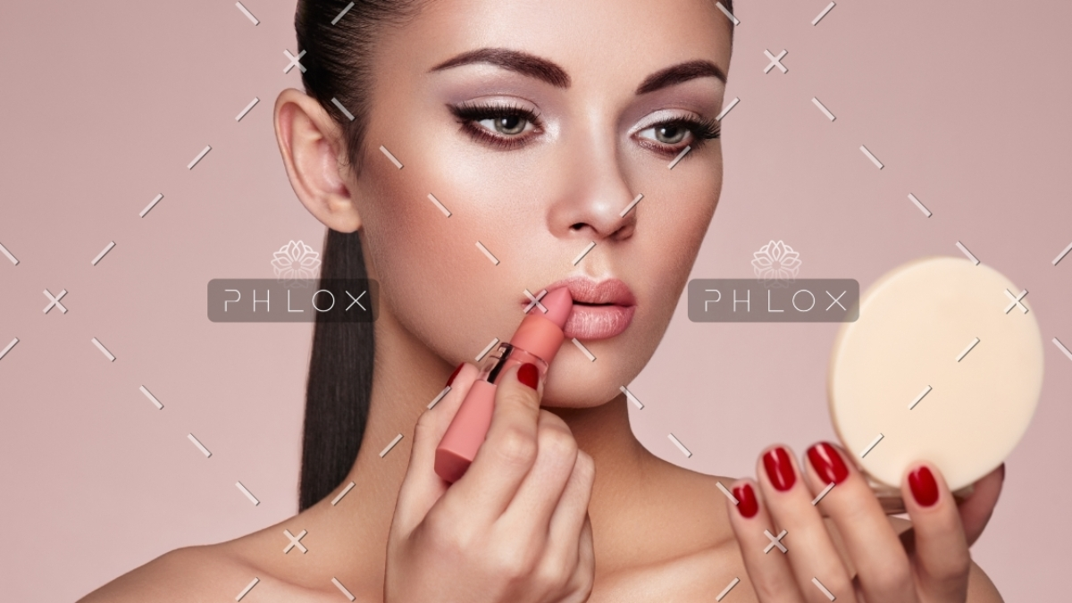 beautiful-woman-paints-lips-with-lipstick-PMB6YWP-1